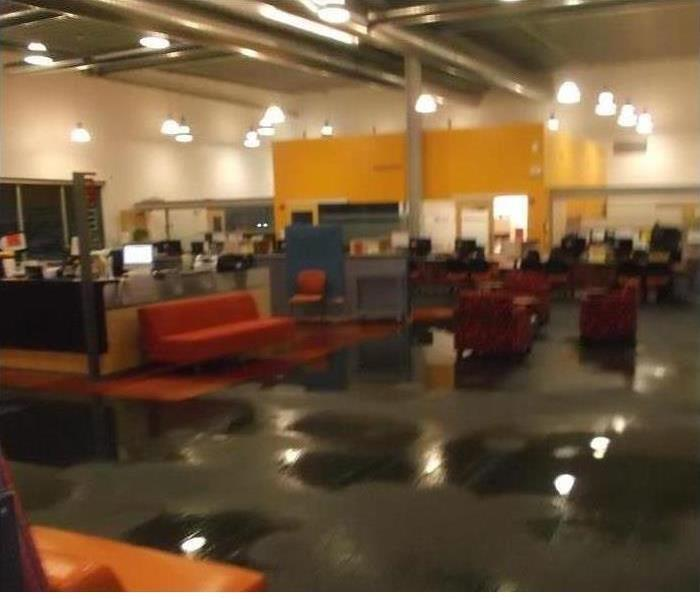 open office area with furnishings and large puddles of water on the floor