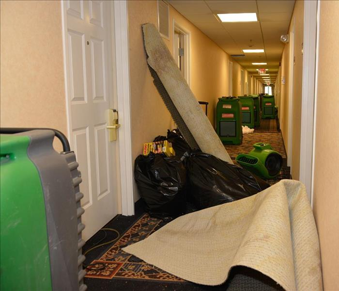 equipment and stacked carpets and debris in corridor