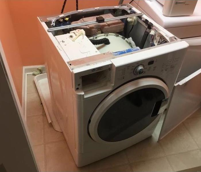 Wet laundry room floor with broken washing machine