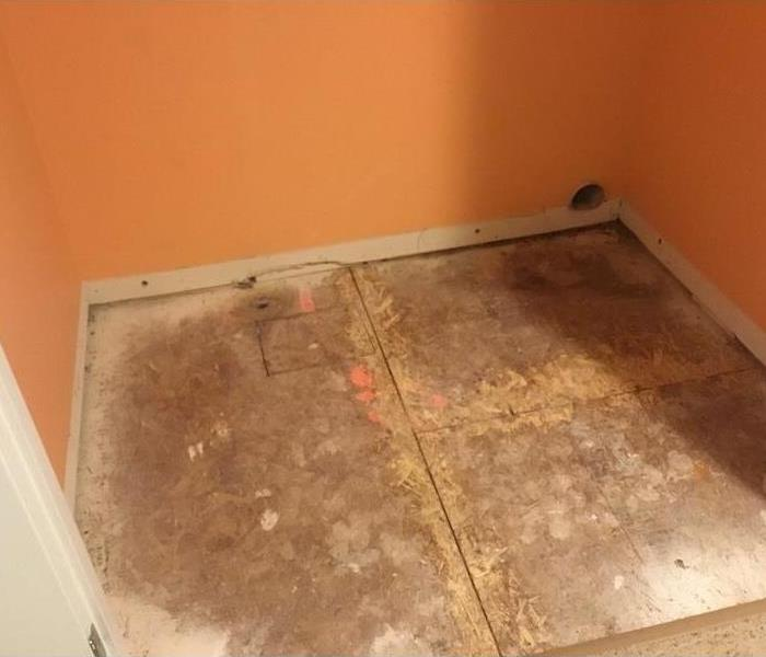 Dried laundry room floor with subfloor showing