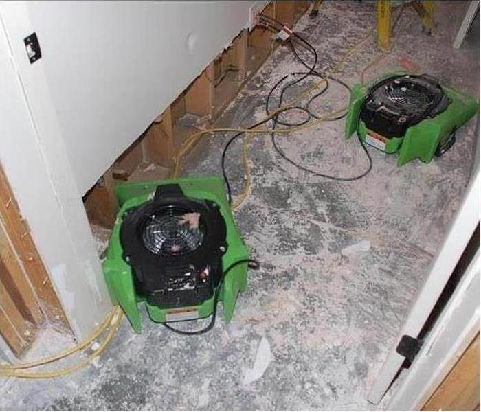 Water damaged wall and floor being dried with SERVPRO equipment