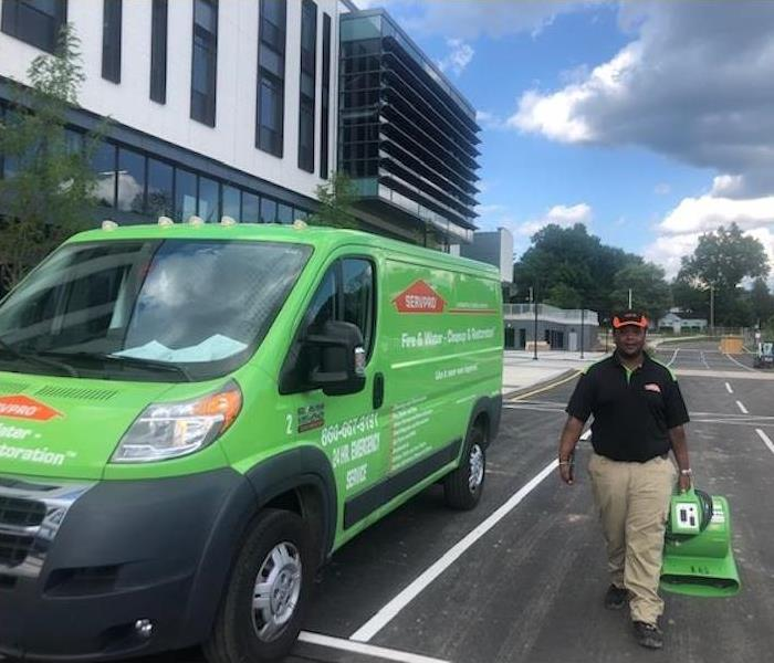 SERVPRO van in parking lot with their employee walking with equipment.