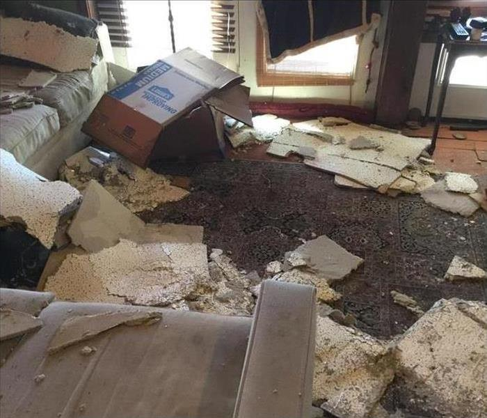 A room with a ceiling that gave way and debris all over the floor after a storm