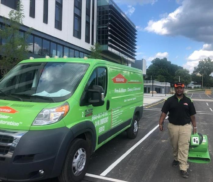SERVPRO technician, holding equipment, walking beside SERVPRO van