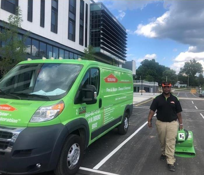 SERVPRO vehicle and technician outside job site.