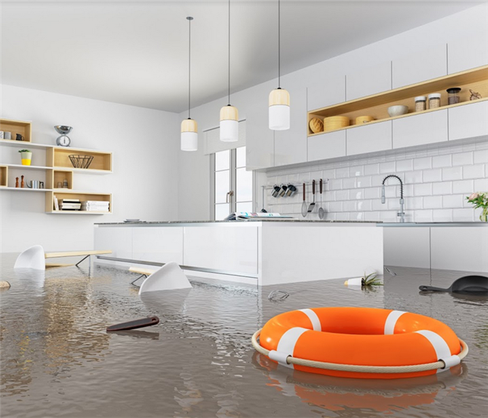 flooded kitchen with items floating in it