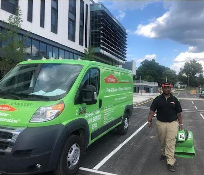A SERVPRO vehicle parked with a SERVPRO employee standing next to the vehicle.