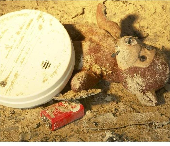 after a fire- fire alarm with battery out and stuffed animal laying in debris